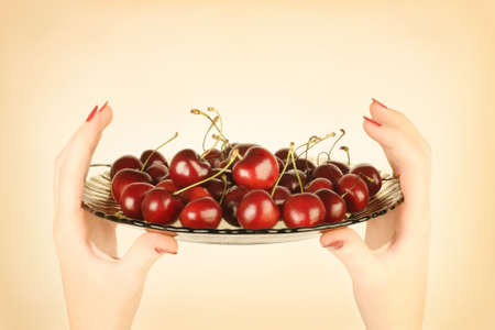 Cherry bowl in hand. Dessert with sweet ripe cherries in the plate photo