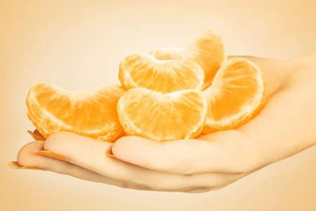 Tangerine slice. Hand with mandarin peeled and sliced photo