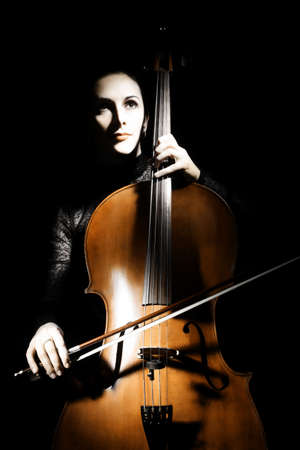Cello classical musician cellist performer. Woman with musical instrument on black background photo