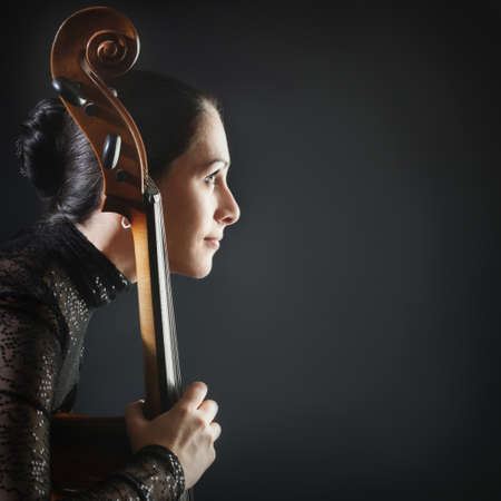 Inspired woman profile cello. Beautiful cellist classical musician with musical instrument photo