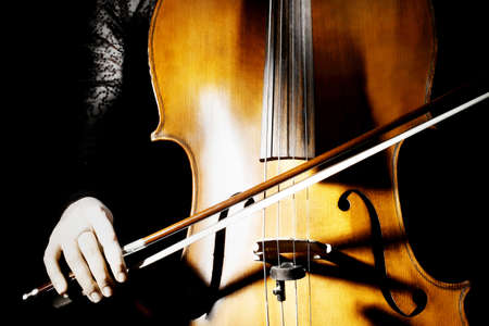 cellist: Cello musical instrument closeup with cellist hand on black background Stock Photo
