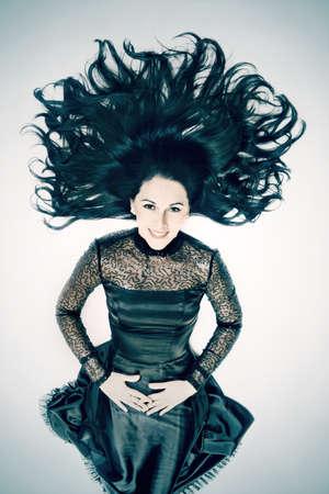 elegante: Jeune femme souriante brunette avec belle portrait de cheveux de mode en noir