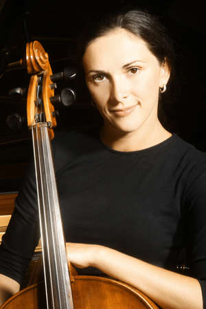Portrait of woman with cello  Pretty smiling musician with musical instrument photo