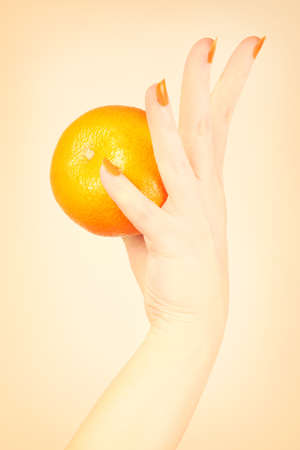 Orange manicure nails Hand with tangerine. Stock Photo - 16310633