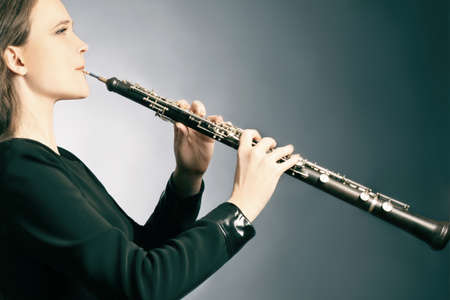 Classical musician oboe playing. Oboist with musical instrument photo