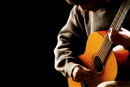 Guitarist musician guitar acoustic playing. Young man performer on black background photo