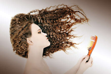 unruly: Curly woman combing hair. Brunette with broken comb wavy hairstyle Stock Photo
