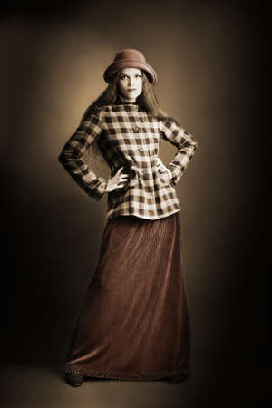 Retro woman in vintage autumn clothes. Fashion model in long skirt hat and checkered jacket in sepia photo
