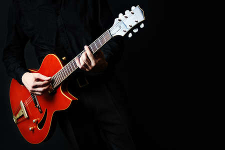 Guitar electric Guitarist playing red music instrument in hands closeup on black Banco de Imagens