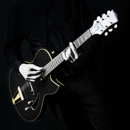 Guitar electric Guitarist playing black music instrument in hands closeup on black