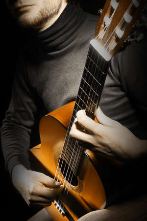 Acoustic guitar player guitarist with instrument closeup photo