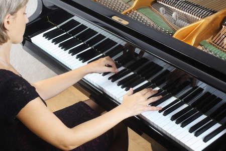 pianista: Piano pianista tocando jugador. Mujer con el primer instrumento musical