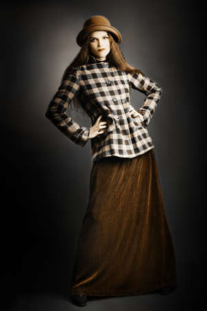 Retro woman in vintage fashion clothes. Model in long skirt, hat and checkered jacket Standard-Bild