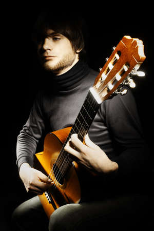 Acoustic guitar guitarist player. Classical musician with musical instrument on black photo