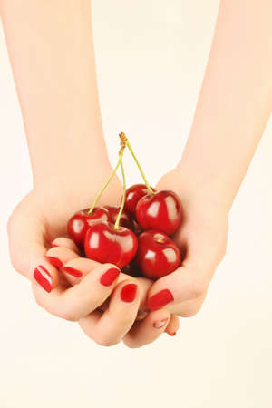 Hands with cherry. Cherries in the womans hand with red nails manicure photo