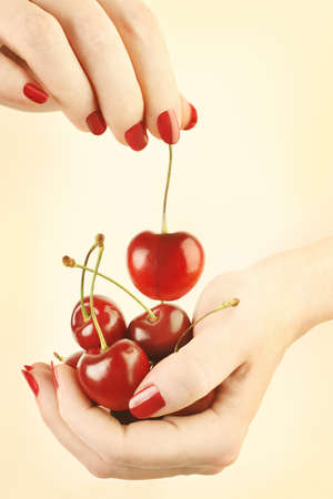 Hands cherry with red nails manicure. Cherries in the womans hand photo