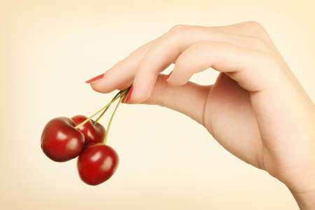 Hand with cherry. Ripe cherries in the womans hand with red nails photo