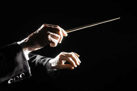 Orchestra conductor hands baton  Music director holding stick