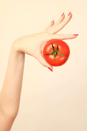 Hand tomato with red nails manicure  Healthy vegetable in the woman photo