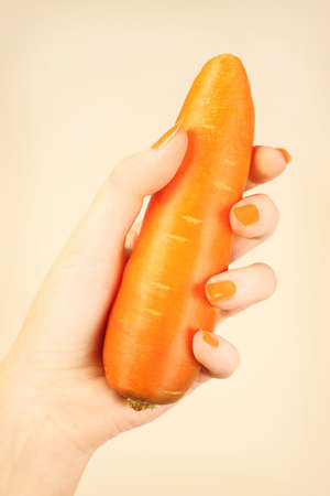 Hand carrot with orange nails manicure  Healthy vegetable in the woman photo