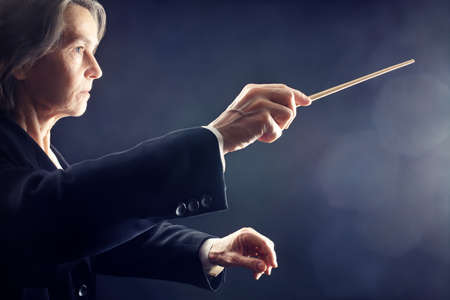 conducting: Orchestra conductor music conducting hands with baton on black Stock Photo