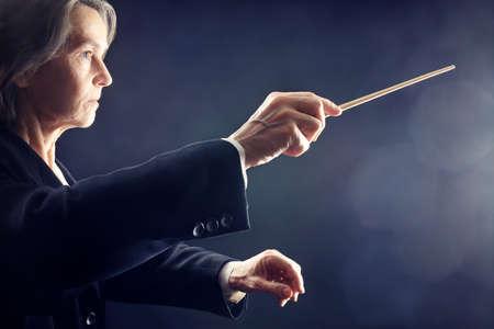 orquesta: Orquesta de m�sica conductor la realizaci�n de las manos con el bast�n en negro Foto de archivo