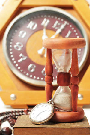 timescale: Hourglass and clock  Still-life with old retro vintage watches Stock Photo