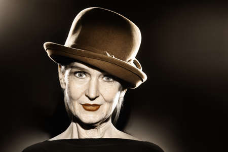 60 65 years: Elegant senior woman in hat fashion portrait  Pretty mature lady 60 years old in retro style Stock Photo