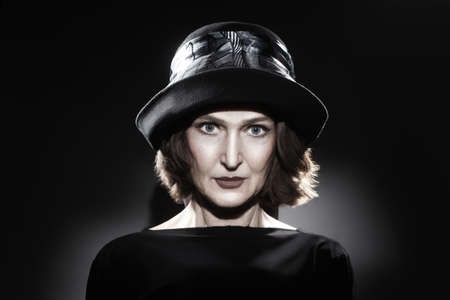 60 years old: Elegant mature woman in hat fashion portrait  Beautiful senior woman portrait 60 years old on black