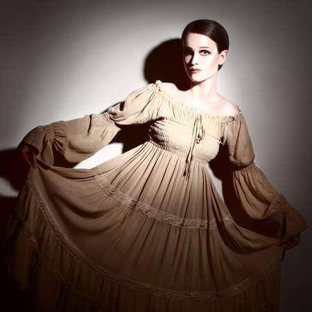 bell bottomed: Elegant woman in beige dress  Young romantic model portrait in darkness