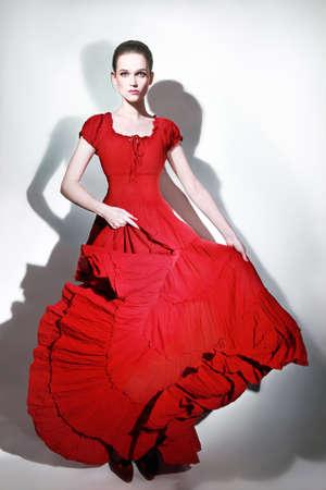 Fashion model in red dress  Elegant woman in long flying dress  Lady in red