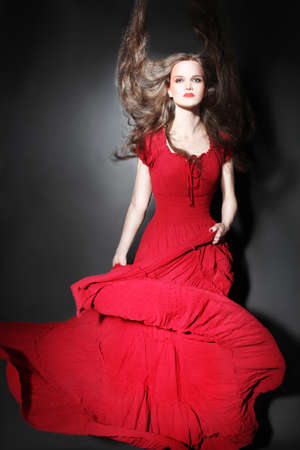 Fashion woman in red dress  Elegant fashion model in long flying dress  Lady in red photo