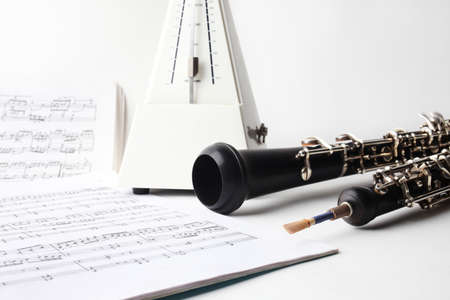 Classical music instrument oboe playing  Musical still-life with instruments, music sheet and metronome photo