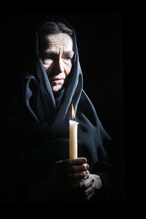 Sad old woman Senior woman in sorrow with candle depressed portrait Stock Photo