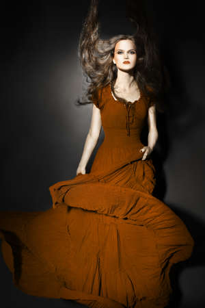 Fashion model in long dress  Elegant woman in maxi flying dress photo