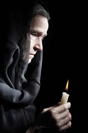 sad old woman: Mujer triste de edad rezo mayor de la mujer con la vela en el perfil chal negro retrato