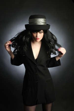 elegante: Femme au chapeau mannequin brune avec des cheveux noirs en robe noire