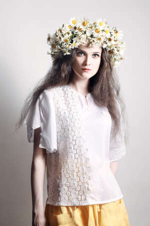 Summer fashion woman Young woman in white with wreath of flowers  Chamomile floral chaplet photo