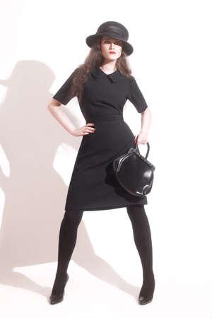 elegante: Femme élégante modèle de mode robe noire dans chapeau avec sac à main