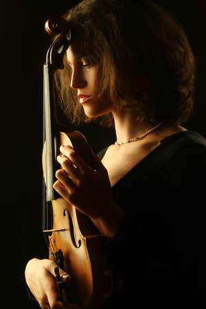 Woman with violin dark portrait of violinist musician 스톡 콘텐츠