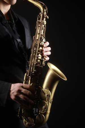 Saxophone classical music instruments Saxophonist with alto sax closeup on black