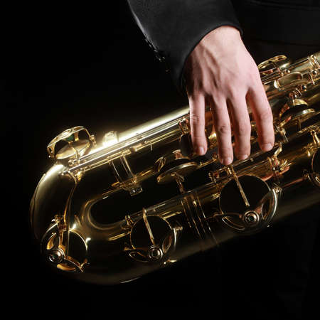 Saxophone jazz music instruments details. Baritone sax with hand of saxophonist closeup on black