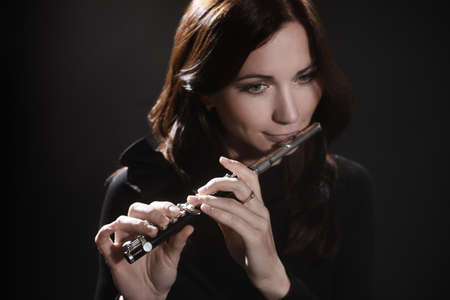 Woman with flute piccolo flutist playing music instrument