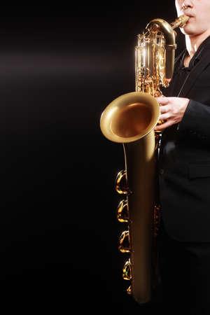 saxophonist: Saxophone jazz musical instruments Saxophonist with Baritone sax details closeup on black