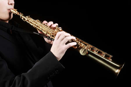 Saxophone soprano musical instruments with saxophonist hands closeup isolated on black