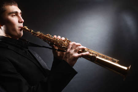soprano saxophone: Saxofonista. Saxofonista con saxo soprano Hombre con instrumentos musicales