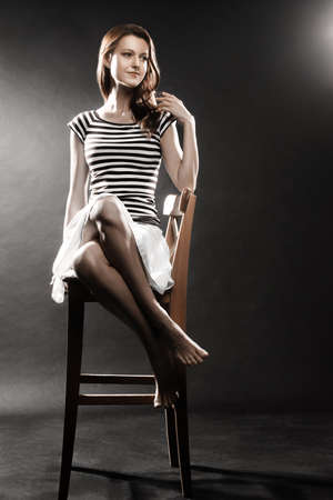 falda corta: Muchacha del marinero Mujer en Mujer del marinero estilo chaleco rayado sentada en la falda corta silla de salón