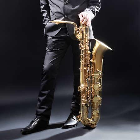 saxofón: Hombre del jazz con el saxofón Jugador Saxofonista con saxo barítono Foto de archivo