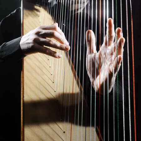Harp strings closeup hands. Harpist with Classical Music Instrument Foto de archivo