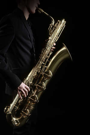 saxophone: Saxophone Jazz Music Instruments Saxophonist with Baritone Sax player isolated on black Stock Photo